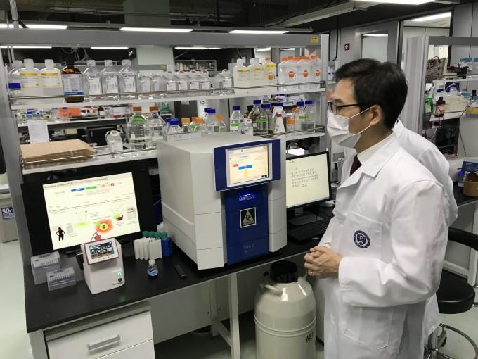 천진우 기초과학연구원(IBS) 나노의학 연구단 단장이 직접 개발한 나노 PCR 진단 기기(모니터 앞)에 대해 설명하고 있다. 오른쪽에 보이는 커다란 기기가 기존에 쓰는 RT-PCR 기기다. 김우현(mnchoo@donga.com)
