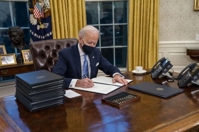 조 바이든 미국 대통령이 20일(현지 시간) 취임식 직후 백악관 집무실에서 각종 행정명령에 서명하고 있다. 바이든 대통령은 서명하는 중에도 얼굴에 마스크를 착용했다.연합뉴스 제공