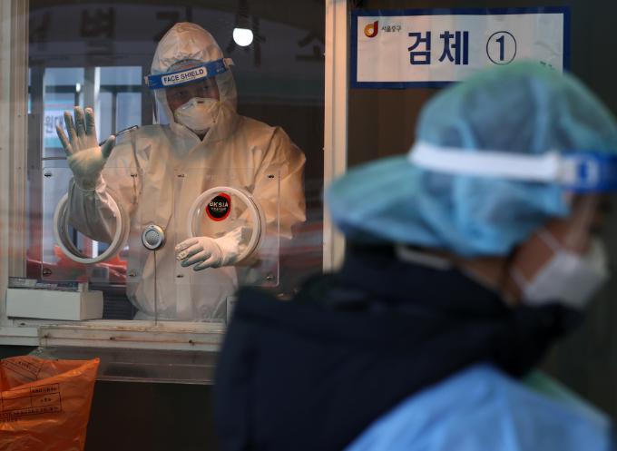 설날인 12일 오전 서울역에 설치된 중구임시선별진료소에서 의료진이 검체 대기자를 향해 손을 들어보이고 있다. 연합뉴스