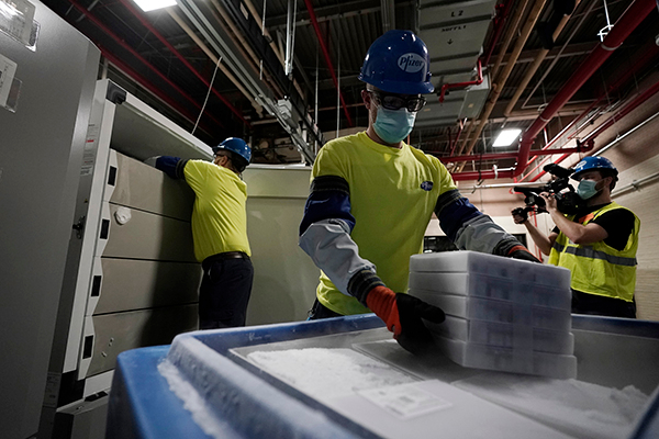 미국 미시간주 포티지에 있는 화이자 공장에서 2020년 12월 13일(현지시간) 직원들이 화이자·바이오앤테크의 코로나19 백신 상자를 운송용기에 싣고 있다. EPA/연합뉴스 제공
