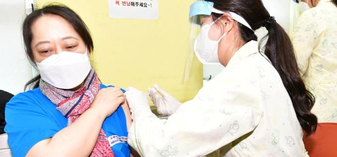 신종 코로나바이러스 감염증(코로나19) 백신 접종이 시작된 26일 오전 광명시보건소 접종실에서 첫 접종자인 강경희(52) 씨가 백신 주사를 맞고 있다. 연합뉴스 제공