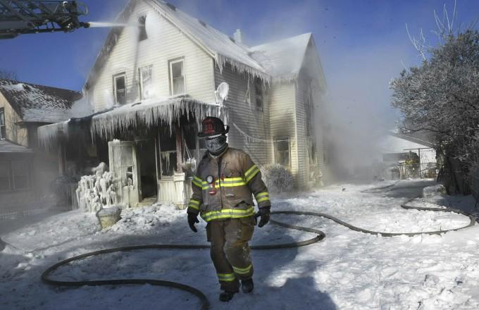 미국 미네소타주에 한파가 찾아온 모습. 화재 진압 현장의 소방관과 얼어있는 집이 보인다. AP/연합뉴스 제공