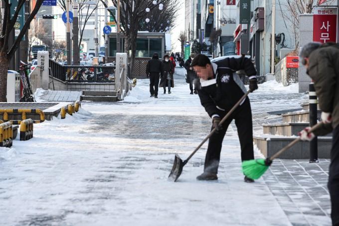 밤사이 서울 지역에 눈이 내린 4일 오전 서울 강남구 학동역 인근 거리 상가 관계자들이 거리의 눈을 치우고 있다. 연합뉴스 제공