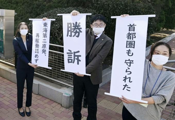 18일 오후 미토지방재판소 앞에서 도카이 제2원전 재가동 금지를 청구한 소송에서 이긴 원고들이 ′승소′ 등의 문구가 적힌 손팻말을 들고 있다. 연합뉴스 제공