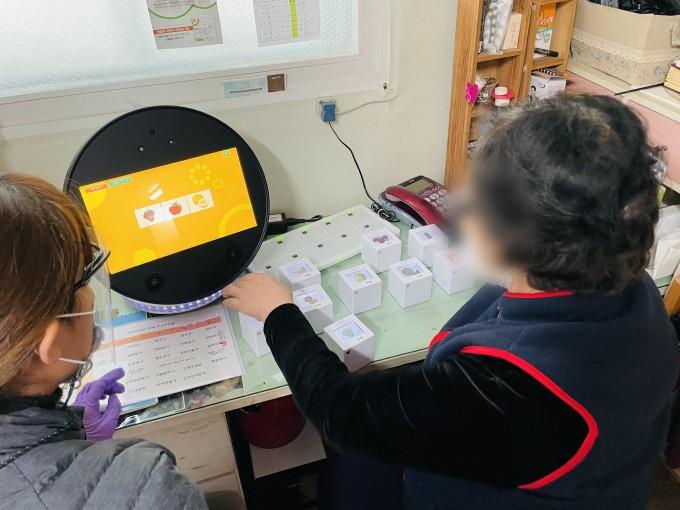 훈련로봇 ′보미′를 이용해 치매 예방 인지 훈련을 진행하고 있다. 이대목동병원 제공