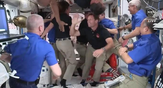 24일 오후(한국시간) 국제우주정거장(ISS)에 도착한 우주인 4명을 ISS에 체류중이던 우주인들이 반갑게 맞이하고 있다. 파란색 옷을 입은 이들이 기존 우주인들이며 검정색 옷을 입은 우주인들은 이번에 ISS에 도착한 우주인들이다. NASA 제공.