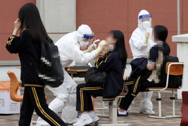 22일 오후 광주 북구 한 고등학교에 설치된 임시 선별진료소에서 학생들이 코로나19 검사를 받고 있다. 연합뉴스 제공