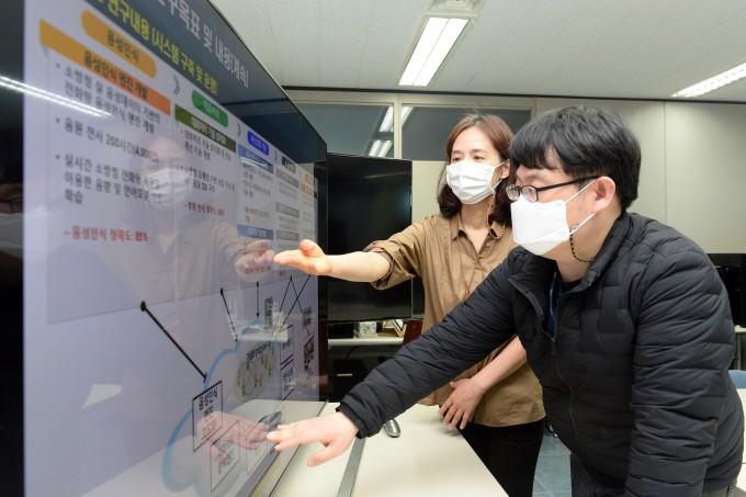 권은정 ETRI 책임연구원(왼쪽)과 박현호 선임연구원이 지능형 119 신고 접수시스템 체계를 논의하고 있다. ETRI 제공.