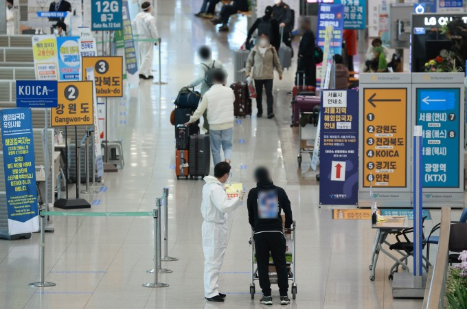 20일 인천국제공항 제1여객터미널 입국장에서 해외 입국자들이 방역절차에 따라 이동하고 있다.연합뉴스 제공