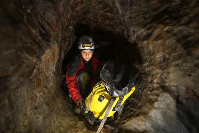 딥 타임 프로젝트에 참가한 한 여성이 좁고 축축한 지하동굴에서 가방을 들고 이동하고 있다. HAI 제공.