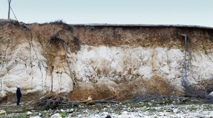 우경식 교수가 해안분지의 지층을 보고 있다. 쌓인 흙 아래로 화강암이 드러나 있다. 이광춘 제공