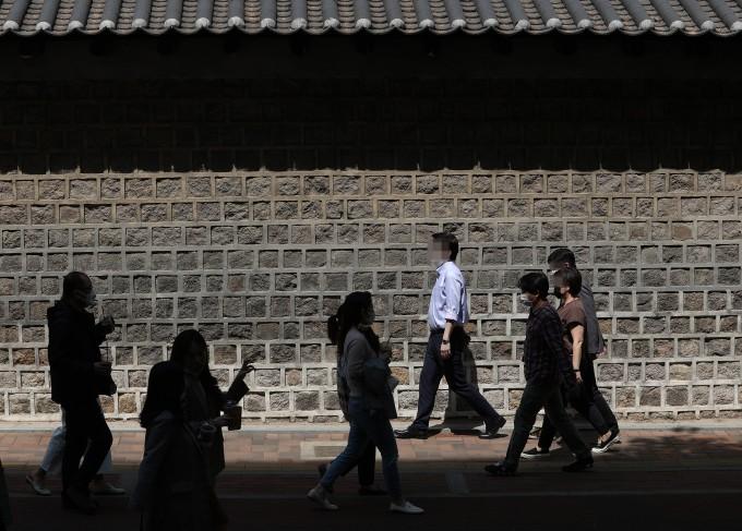 전국적으로 낮기온이 크게 오른 19일 오후 서울 중구 덕수궁 돌담길에서 시민들이 점심 후 산책을 하고 있다. 연합뉴스 제공