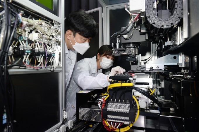 주지호 ETRI 선임연구원(왼쪽)과 이찬미 연구원이 세계 최초로 개발한 공법인 마이크로 LED용 동시 전사 접합 공정을 수행하는 있다. ETRI 제공.