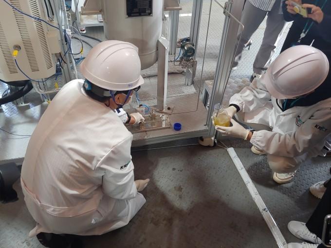 연구팀이 플랜트 설비에서 나오는 나프타를 비커에 받고 있다. 대전=조승한 동아사이언스 기자 shinjsh@donga.com