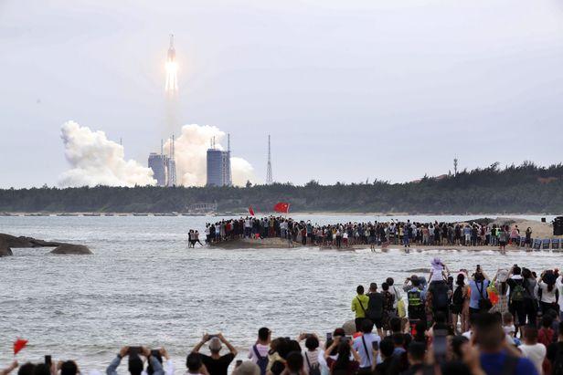 2021년 4월 29일 중국 하이난성 원창 기지에서 우주정거장 핵심 모듈 톈허를 실은 창정 5B 로켓이 발사되는 모습을 주민들이 지켜보며 사진을 찍고 있다. 모듈 톈허는 우주정거장의 궤도를 유지하기 위해 추진력을 내는 기능과 함께 향후 우주 비행사들이 거주할 생활 공간을 갖추고 있다. 중국은 올해와 내년에 모두 11차례 걸친 발사로 모듈과 부품을 실어날라 자국 독자로 우주정거장을 건설한다는 계획이다. 연합뉴스 제공