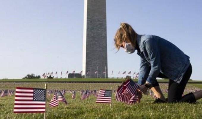 미국 워싱턴DC의 내셔널몰 워싱턴기념비에서 한 여성이 코로나19 사망자를 추모하기 위해 미국 국기를 꽂고 있다. EPA/연합뉴스 제공
