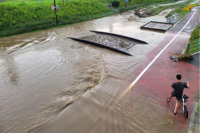 서울 일부 지역에 강한 소나기가 내린 15일 오후 서울 강동구 상일동 고덕천에서 한 시민이 물이 고인 자전거 도로를 지나가고 있다. 연합뉴스 제공