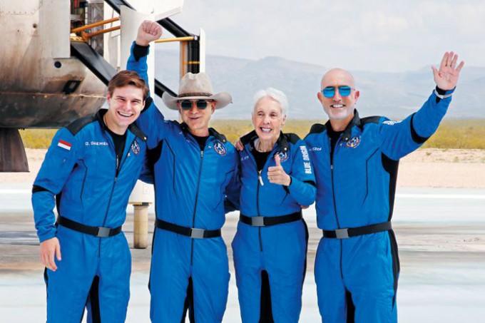제프 베이조스(왼쪽에서 둘째)가 20일 자신이 설립한 우주 탐사 기업 블루 오리진의 뉴 셰퍼드 로켓을 타고 고도 100㎞ 이상에서 우주여행을 마친 뒤 지구로 귀환해 탑승자들과 손을 흔들며 기뻐하고 있다. 왼쪽부터 18세 네덜란드 청년 올리버 데이먼, 베이조스, 82세 퇴역 여성 조종사 월리 펑크, 베이조스의 동생 마크 베이조스. 로이터/연합뉴스 제공