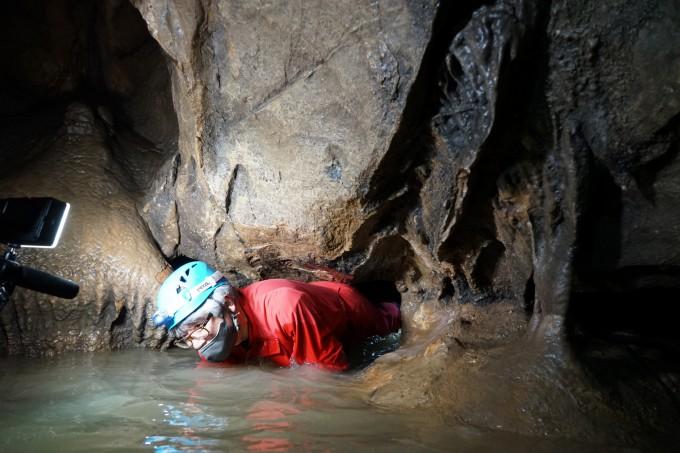 -개구멍을 통과하는 '파고캐고 지질학자'의 필자 우경식 교수. 개구멍을 통과하면 본격적으로 화려한 동굴 풍경이 시작된다.
