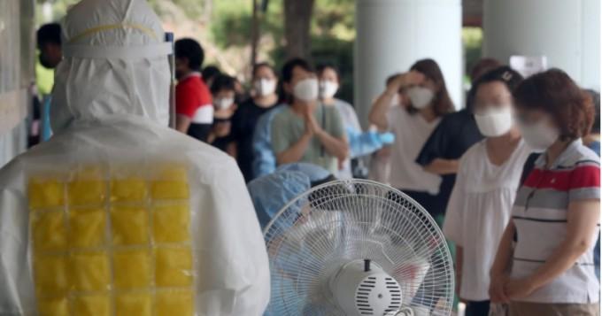 무더위 속에서 보건소 직원이 얼음 조끼를 착용하고 코로나19 검사를 진행하고 있다.  연합뉴스 제공